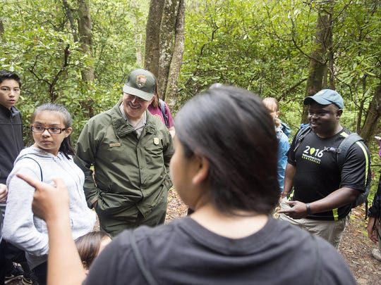 Blue Ridge Parkway Superintendent Mark Woods, left, and superintendent of the Great Smoky Mountains National Park Cassius Cash, right, talk with Cherokee middle students on a hike through the Deep Creek in the Smokies last week. Record visitation at the parkway and the Smokies has led to an increase in economic impact in local communities.