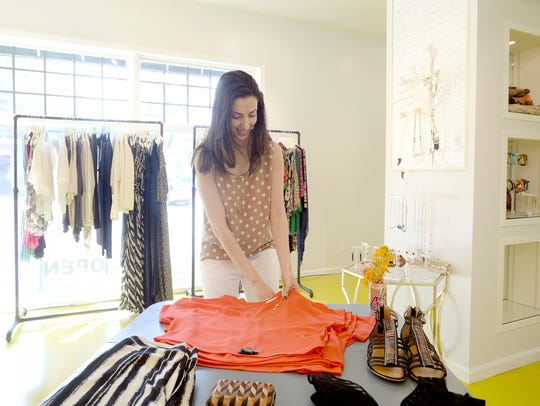 Asheville native Dema Badr folds clothing as she talks