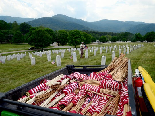 The bed of a John Deere is filled with rolls of small American flags as groundsman Jerry Massey works to put a flag on every grave at the Western Carolina State Veterans Cemetery in Black Mountain on Thursday, May 27, 2016. Massey said he and his crew will put out more than 5,000 flags in honor of Memorial Day.
