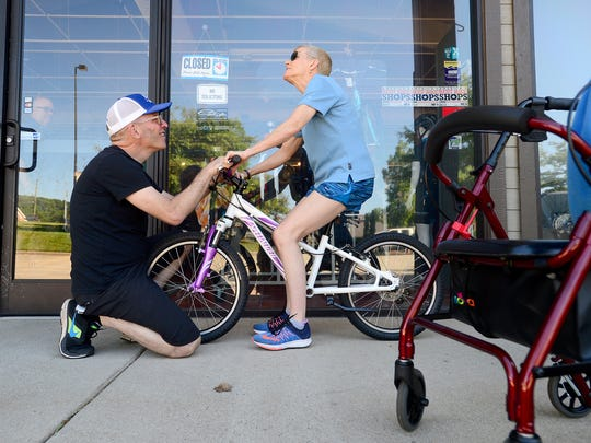 """Rich Slingsby, of Motion Makers Bicycle Shop, helps Virginia """"Gin"""" Oman with her balance as she practices with her Specialized bicycle at the Asheville store on Thursday, June 9, 2016. Oman, who is living with Multiple Sclerosis, uses a walker to get around but has worked up to walking with trekking poles and unassisted at home and is now on a quest  to ride a bicycle."""