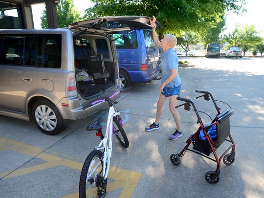 """Virginia """"Gin"""" Oman loads her Specialized brand bicycle into the back of her vehicle after a lesson at Motion Makers Bicycle Shop in Asheville on Thursday, June 9, 2016. Oman, who has Multiple Sclerosis, can load the bicycle without any help."""