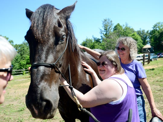 Amber Bryant, left, pets Dharma with help from Kathy Tustanowski, right, during a horse therapy session with Equinox Horse Foundation celebrating national deaf-blind awareness month at Shaman Hill farm on Friday, June 10, 2016. Participants groomed the horses and then rode them with help from guiding volunteers.
