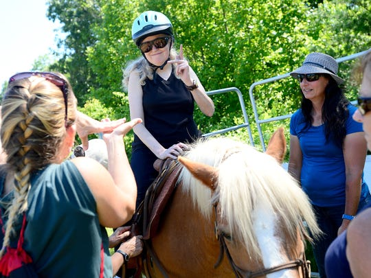 Jamie Henderson talks with her licensed certified interpreter Kathleen Speckhardt, left, from atop a horse as horse therapist Lori Araki, right, gives instruction as they start a session with Equinox Horse Foundation celebrating national deaf-blind awareness month at Shaman Hill farm on Friday, June 10, 2016.