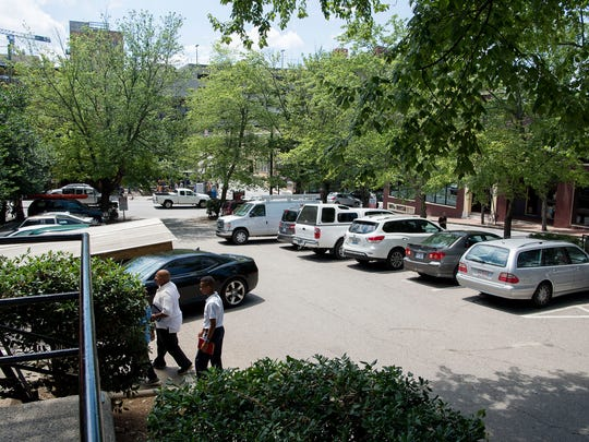 Visitors pay parking at a meter while a car parks into