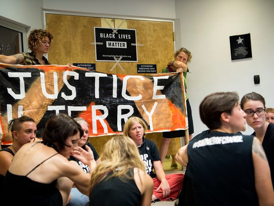 "Community members and organizers from Showing Up for Racial Justice sit inside the lobby of the Asheville Police Department discussing white privilege and cycles of discrimination against people of color Thursday morning July 21, 2016. Those participating will sit in until the police meet their demands- accountability in the killing of Jerry ""Jai"" Williams and an end to police violence towards people of color- or until they are arrested."