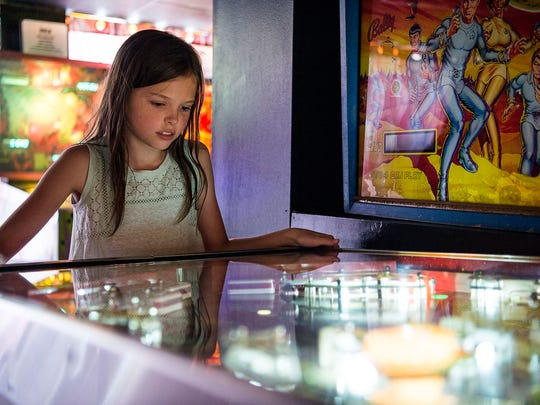 Ann Redman, 9, of Mars Hill, plays a the pinball game Circus during her first time to the Asheville Pinball Museum in July 2016.