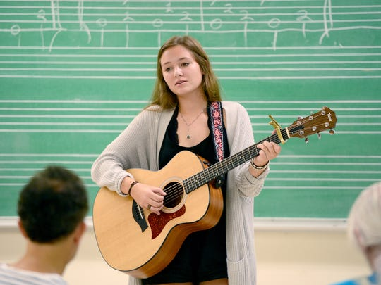 Emma James, of Charlotte, performs a song on the guitar for the class during country and bluegrass singer Kathy Mattea's workshop at Warren Wilson College during the Swannanoa Gathering on Wednesday, July 27, 2016.