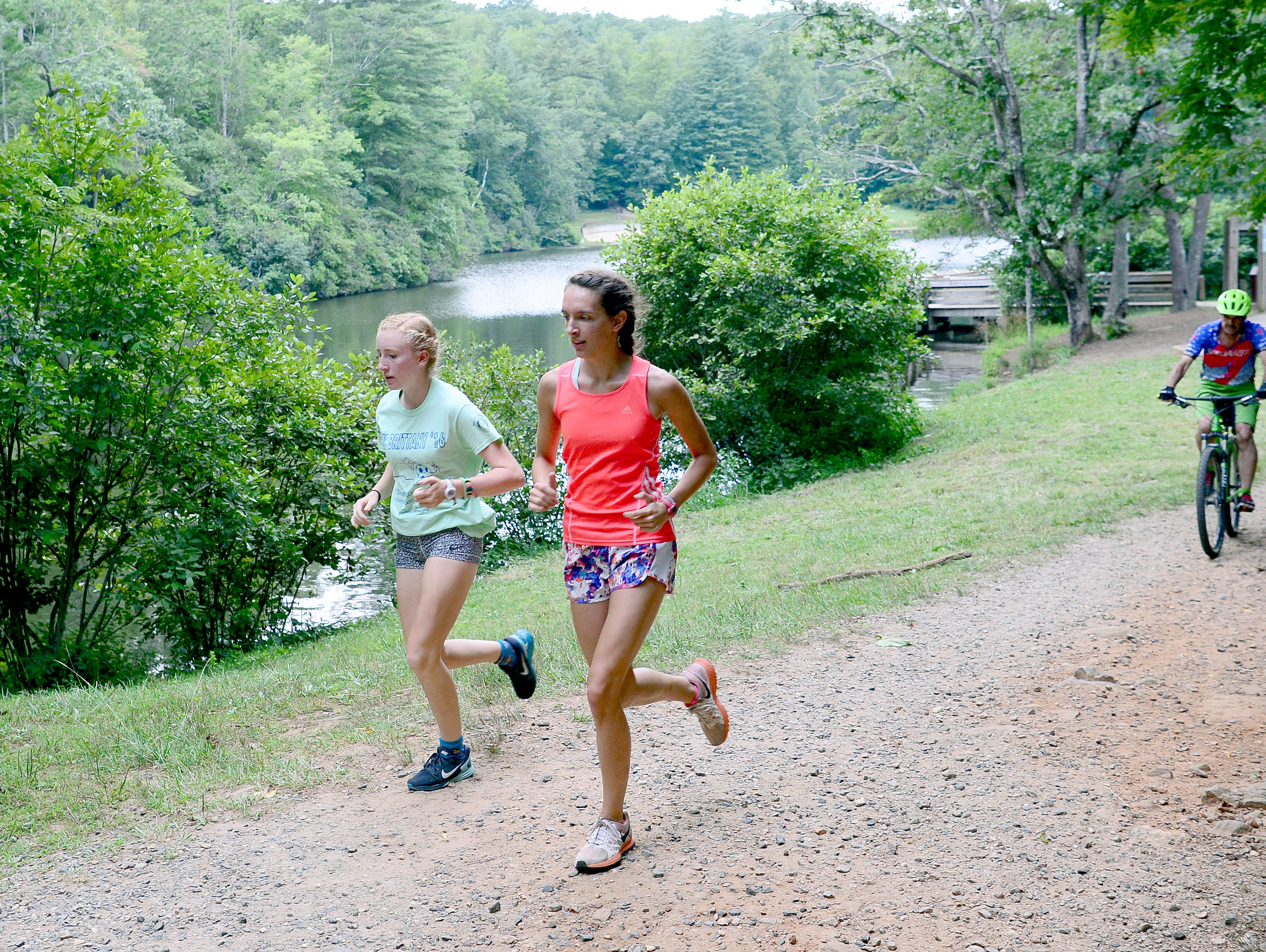 Roberson cross country runners Sarah Lewis, left, and Elise Wright, right, lead the pack as the team does a workout run at the North Carolina Arboretum and Lake Powhatan on Thursday, Aug. 4, 2016.