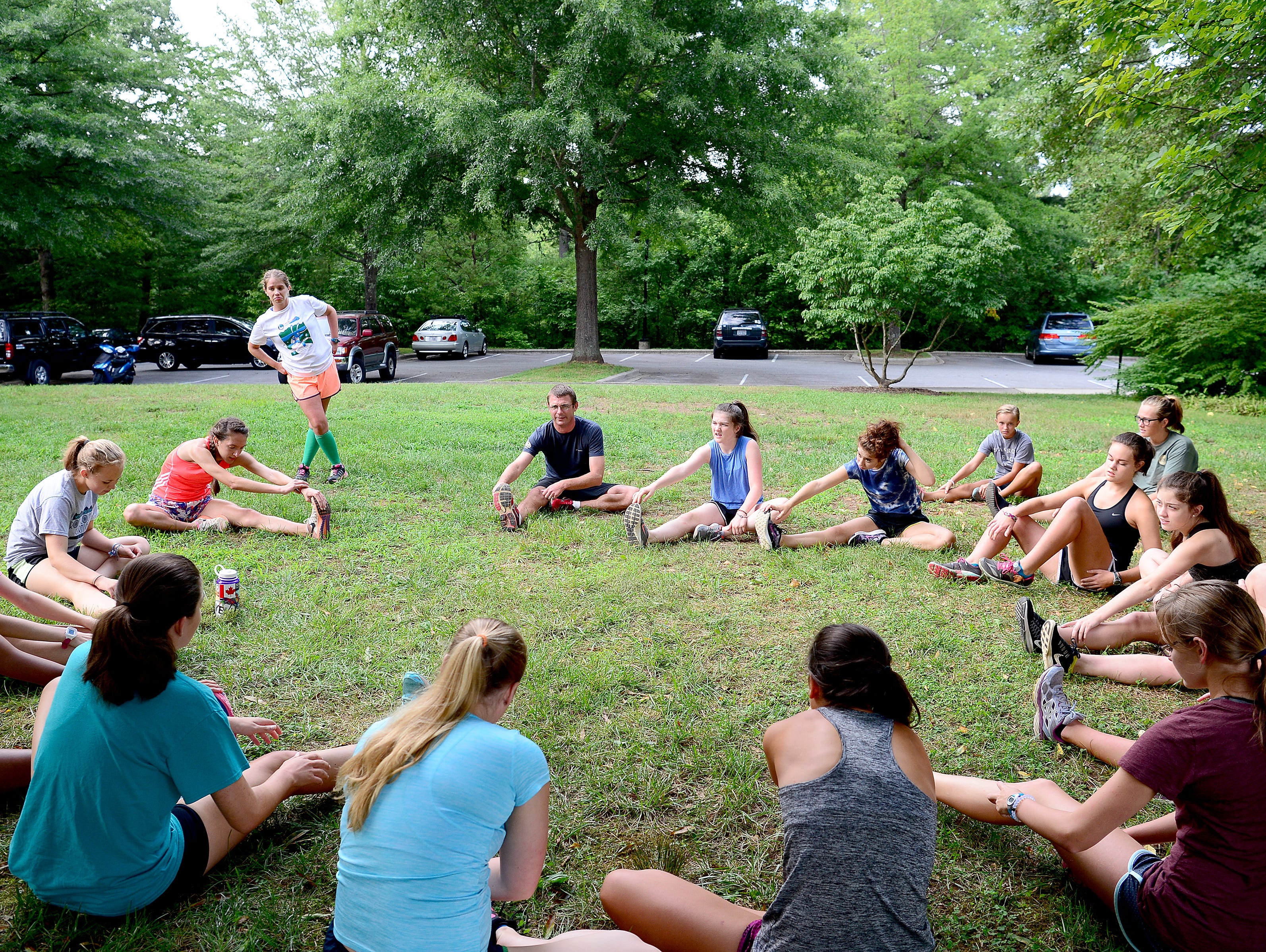 Members of the Roberson girl's cross country team stretch before a workout run at the North Carolina Arboretum on Thursday, Aug. 4, 2016.
