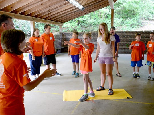Marissa Livingston, 11, of Dupont, and Asheville Citizen-Times intern Claire Hansen direct a group of campers from the conductor mat as they create a beat with claps and hums during a music therapy session at Camp Heart Songs at Camp Tekoa in Hendersonville on Saturday, Aug. 13, 2016. The camp, which is in it's 13th year, is an overnight camp for children experiencing grief.