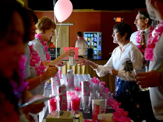 Dianna Traylor buys a glass at the Pink Pint Night table at Highland Brewing Company on Wednesday, Oct. 6, 2016. Proceeds from the event benefitted Ladies Night Out, a program that gives free physicals and mammograms for underinsured women.