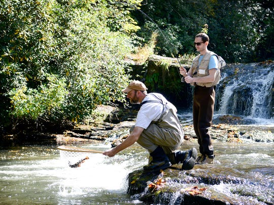 Matt Christian, an education specialist with the North Carolina Wildlife Resources Commission, scoops up a trout caught of Giles Simpson, of Wilmington, on the East Fork of the French Broad River near Rosman. Simpson made the drive from Wilmington to learn how to fly fish.