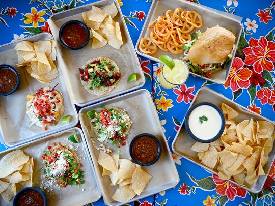 A selection of tacos at Mamacita's Taco Temple include (clockwise from top) the Baja taco, taco al pastor, borracha taco, and tinga taco, shown with a tinga torta and chips and queso.