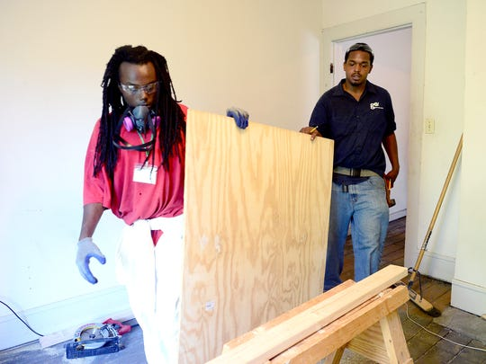 Martell Zander, left, and Eric Howell, a construction job training instructor, place a piece of plywood on a sawhorse so they can cut it to size while working with the Green Opportunities Build carpentry program on Thursday, Aug. 25, 2016.