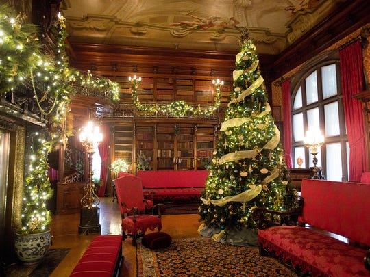 A Christmas tree, greenery and lights decorate the inside of the library in the Biltmore House.