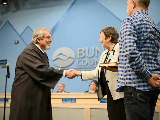 Peggy Buchanan is sworn in to the Buncombe County School Board by Judge Marvin Pope as her son, Ben Keith, holds the bible for her at the Buncombe County Schools central office on Thursday, Dec. 1, 2016.