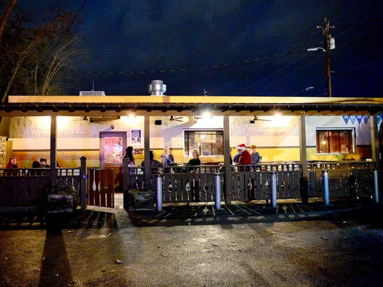 As the night winds down stragglers are left chatting on the porch of The Admiral in West Asheville after their penultimate Saturday night dance party on Saturday, Dec. 17, 2016.
