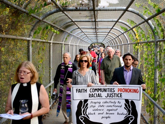 Led by Amy Cantrell, of Be Loved Asheville, left, and sign carriers Rev. Marcia Mount Shoop, of Grace Covenant Presbyterian Church, and Rabbi Justin Goldstein, of Congregation Beth Israel, a group of clergy and community members cross over the Charlotte Street pedestrian bridge on their way to the courthouse during a prayer processional calling for racial justice on Tuesday, Nov. 1, 2016. The group stopped at significant places for prayer and reflection including the former Stephens Lee High School.