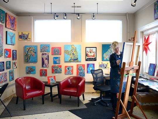 Angela Alexander works on a painting at her studio