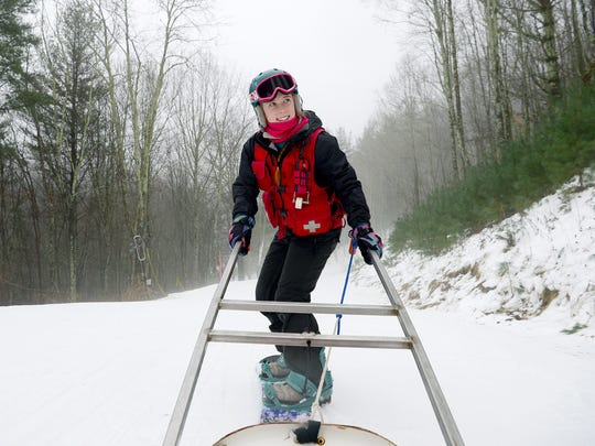 Indigo Hollister, 18, gives a demonstration of how hurt skiers are transported down the mountain on a sled that she pulls on her snowboard at Wolf Ridge Ski Resort on Wednesday, Jan. 11, 2017. Hollister has been working on the ski patrol of two years.