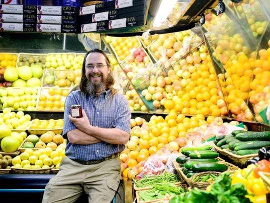 Walter Harrill, of Imladris Farms, holds a jar of his locally-made jam in the produce section of the French Broad Food Co-op in 2016.