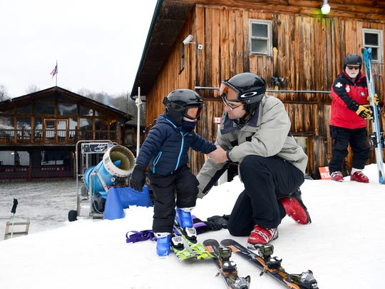 Charlie Schieren, of Asheville, helps his son, Walker, 4, into his skis at Wolf Ridge Ski Resort on Wednesday, Jan. 11, 2017. Walker started skiing at the age of 2 and goes down the slopes in front of his dad who holds two ropes around him like a leash.