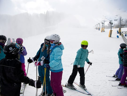 Groups of students wait for instruction before skiing