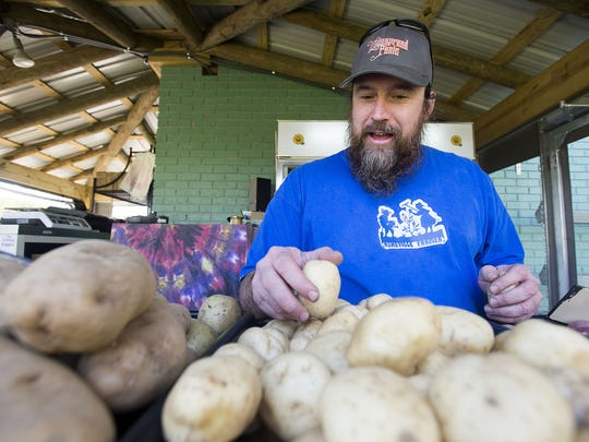 Kendall Huntley of Whispersholler Farms sorts through potatoes at the Asheville Food Park at the corner of Amboy Road and State Street in 2016.