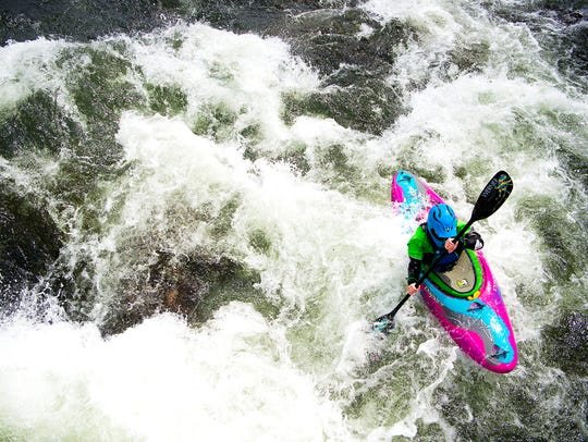 A kayaker paddles through the rapids under a bridge