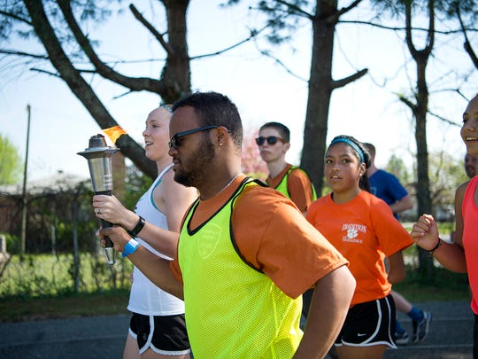Alex Suder holds the Special Olympics torch while jogging around the track during the opening ceremony Friday April 14, 2017. Local law enforcement brought the torch from the county courthouse to East Henderson High.