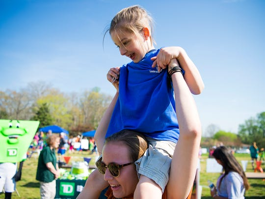 Peyton Hooper, 9, laughs while her buddy West Henderson student Caroline Meadow lifts her up on her shoulders Friday April 14, 2017. The Spring Games included a young athletes area for athletes 2-7 with a ball toss, an obstacle course, and more.