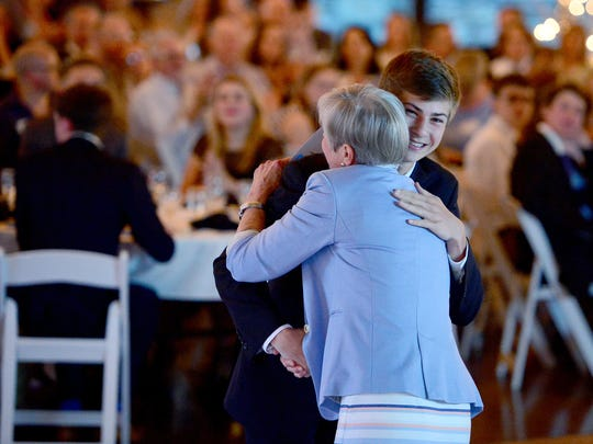 Junior Keaton Roberts hugs interim superintendent Dr. Bobbie Short as he is honored during the Asheville City Schools annual academic awards banquet at the Crest Center on Wednesday, April 19, 2017.