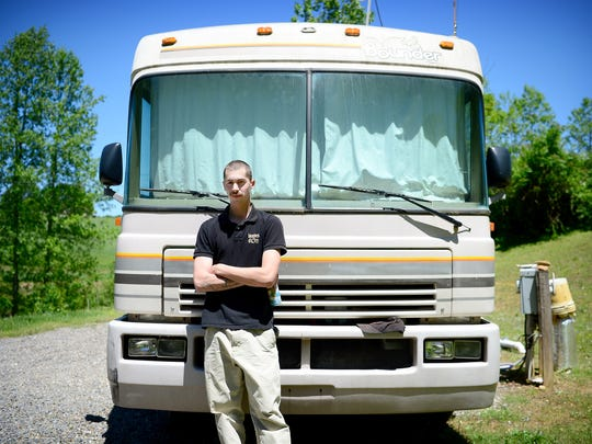 Zacre Poirier, 24, stands in front of the RV he purchased to live in and parks on a friend's land in Clay County. After unsuccessfully searching for housing in the area he grew up in, he bought the RV and restored it to working condition.