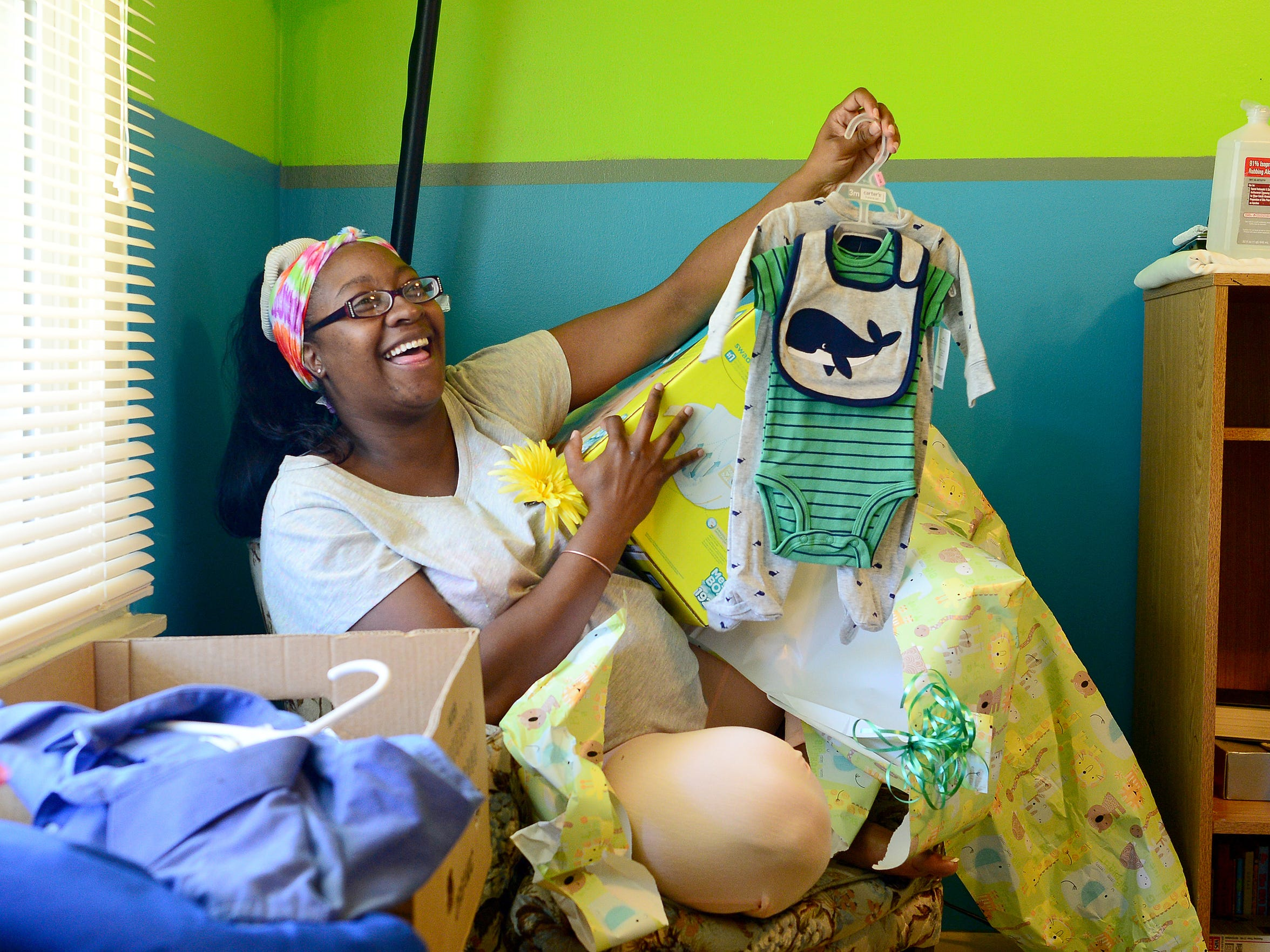 Quella Sharp opens presents during a baby shower held