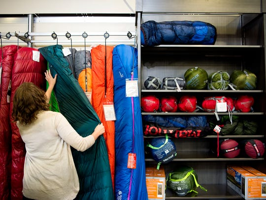 Hannah Myers, marketing coordinator with Diamond Brand Outdoors, sorts through down and synthetic sleeping bags May 9, 2017 in the store, located in South Asheville.