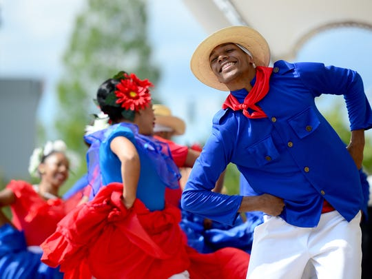 Performers from the Dominican Republic with the M & K Dance Studio perform on the stage at Pack Square Park following a Folkmoot USA parade in downtown Asheville on Friday, July 29, 2016.