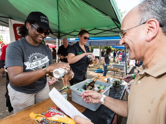 A volunteer pours a sample of beer for a festival goer at last year's Craft Beer Festival. The 2017 festival is June 9 in Fondren.
