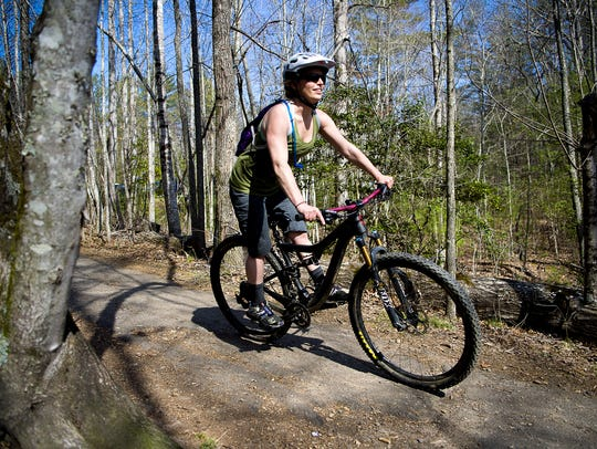 A mountain cyclist rides down a trail at the Bent Creek