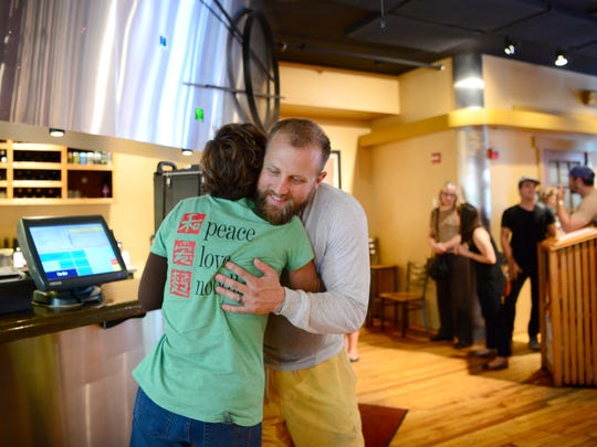 Ellie Feinroth, co-owner of Doc Chey's Noodle House, hugs David Godfrey as he waits for carryout food during lunch service on Thursday, Aug. 3, 2017. Godfrey has done power washing for the owners of the closing restaurant for years.