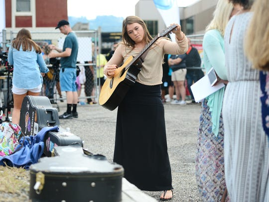Sarah Rininger, of Knoxville, tunes her guitar as she