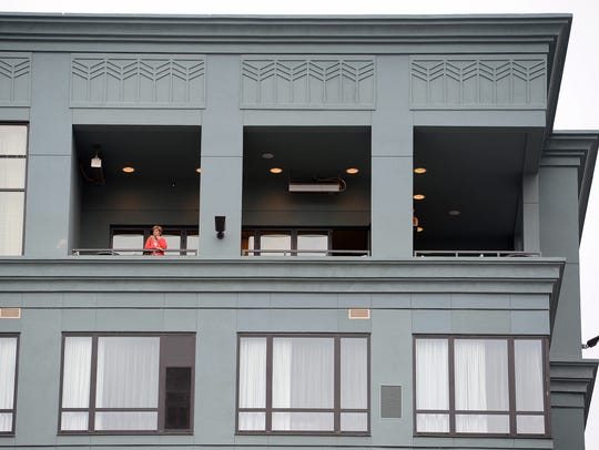 A woman looks out over downtown from the top floor