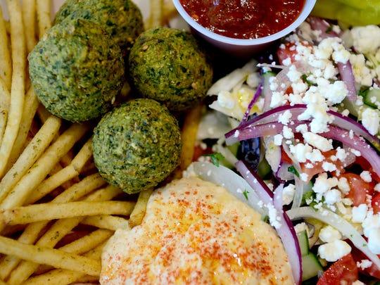 The falafel box at The Doner Kebabs & Falafels inside the Asheville Mall has falafel, herb french fries, a salad of cabbage, lettuce, cucumber, white and red onion, goat cheese, chili tomato sauce and has an added scoop of hummus.