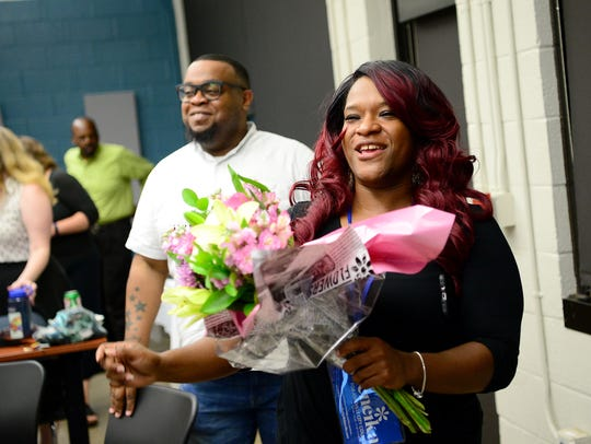 Sheneika Smith receives flowers after officially coming