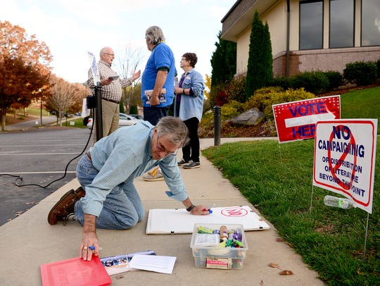 Residents campaign for City Council candidates outside a the St. Eugene Catholic Church polling site in North Asheville Tuesday.
