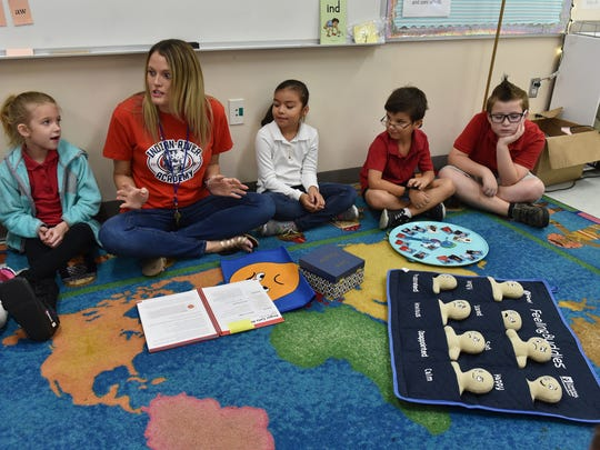 """Second-grade teacher Courtney Antosh (second from left) talks to her class about feelings as students (from left) Brooklyn Jared, Cristina Martinez, Timothy Powell and Rhys Tredor listen Tuesday, Nov. 14, 2017, at Indian River Academy in Indian River County. The class uses tools such as feeling buddies (front right), wish well board (circular plate), safe keeper box and the big feelings cape to keep track of their moods. The safe keeper box contains photos of all the students in class for the day. The wish well board is used to keep track of students not feeling well, and the feeling buddies and feelings cape are used to show emotions. """"It helps the kids to be successful,"""" Antosh said."""