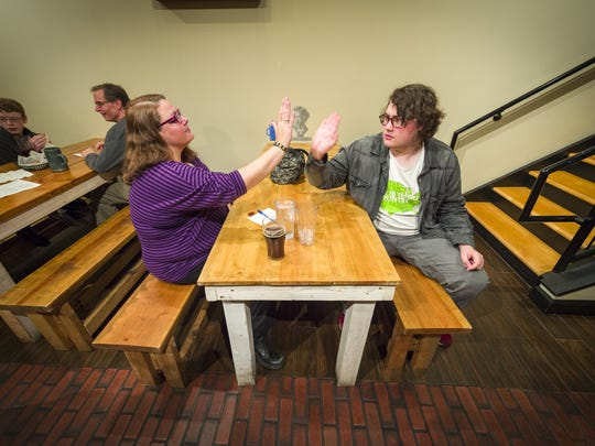 The mother-and-son team of Sarah Hidden, of Plainfield, left, and Aidan Hidden, 17, of Avon, high five during trivia night at Books & Brews in Zionsville, Monday, November 27, 2017.