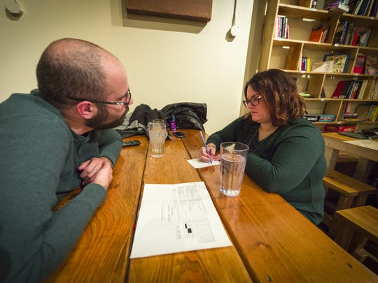 The husband-and-wife team of Jonathan and Danielle Ogilvie, of Zionsville, ponder one of the questions during a round of trivia. Jarrod Bridgeman, one of Central Indiana's best trivia-night hosts, ask trivial questions to teams of players at Books & Brews in Zionsville, Monday, November 27, 2017.