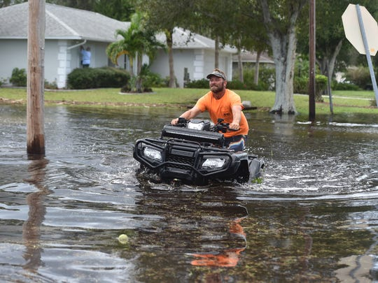Darren House drives is ATV through the floodwaters of Lee Boulevard next to his home on Fort Pierce Blvd. on Monday, Sept. 11, 2017, in Lakewood Park. House was one of dozens of residents using the floodwaters for recreation as kayakers, ATVs, and swimmers made the best of the flooding situation brought on by Hurricane Irma.