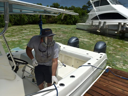 """""""I'm afraid of the fumes,"""" said Austin Kemp, of Central Marine, wearing a gas mask while taking a boat out for a test run in the algae filled waterway of the St. Lucie River on Thursday, June 30, 2016, in Stuart."""
