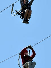 Jeff Greiner (bottom) of Asheville Zipline Canopy Adventures and his son O'Reilly (top), 10, zip down the lines at the Crowne Plaza Resort. O'Reilly, who has autism, will have his own team for a fundraiser for the Autism Society of North Carolina June 2nd.